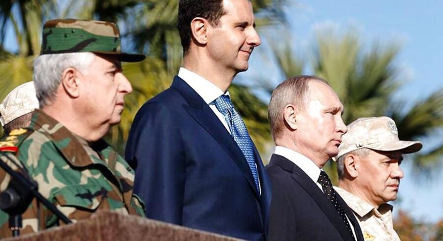 Den russiske præsident, Vladimir Putin og Syriens præsident, Bashar al-Assad overværer en militærparade på den russiske Latakia-flybase i Syrien i december 2017 i selskab med stabschefen for det syriske forsvar, Ali Abdullah Ayyou, (t.v.) samt den russiske forsvarsminister, Sergej Shoigu. Putin er dreven, når det gælder om at øge russisk indflydelse i regionen.