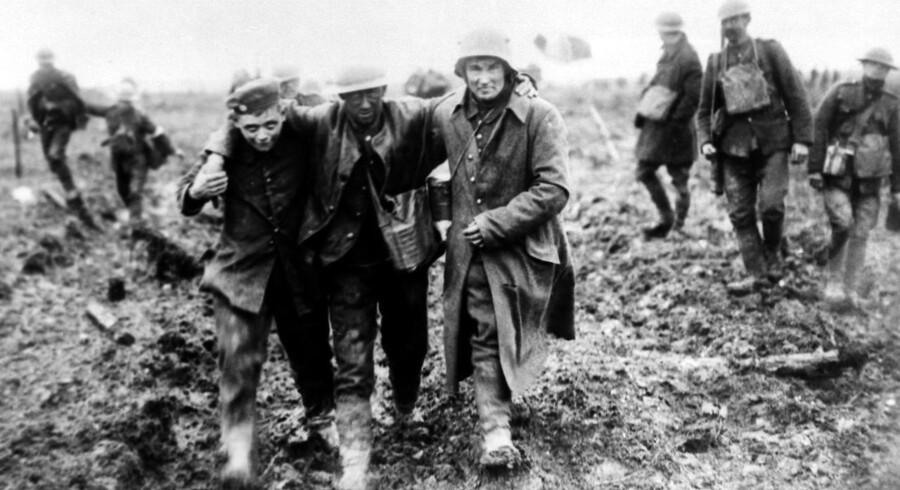 »På 100-årsdagen for Første Verdenskrigs afslutning er der grund til at se tilbage på erfaringerne fra det brutale 20. århundrede,« skriver dagens kronikører. På fotoet ses to tyske soldater hjælpe en såret canadisk soldat ved Slaget ved Vimy i 1917. Foto: AP/Ritzau Scanpix