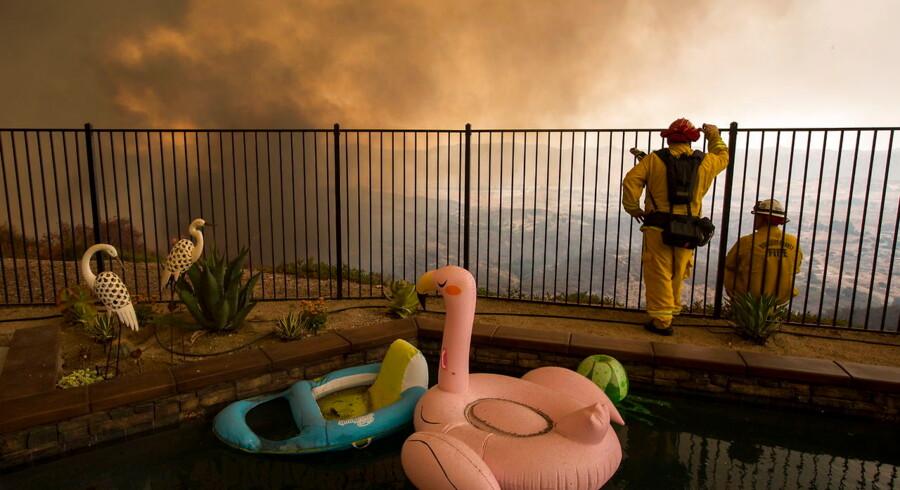 Brandfolk ser ud på skovbrande, som truer private hjem nær Lake Elsinore, Californien i august. 2018 sætter rekord som året med mest omfattende skovbrande nogensinde i Californiens historie. En rekord, som lokale eksperter og myndigheder bl.a. tillægger tørke grundet klimaforandringer.