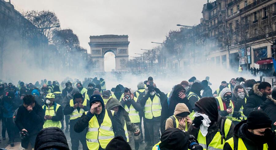 Protestbevægelsen Gule Veste demonstrerer omkring Triumfbuen i Paris. Den franske nationalsang lyder, mens tåregasgranater bliver skudt afsted fra et presset fransk politi. Foto: Asger Ladefoged