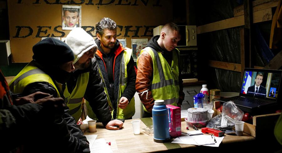 En gruppe fra protestbevægelsen De Gule Veste nær den vestfranske by Bouguenais følger med skeptiske miner præsident Macrons TV-tale.