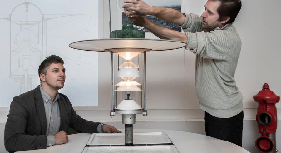 Søren Peter Kristensen og Joakim Wayland (th.) sammen med en prototype på PH's Slotsholmslygte. Forsøget med vand går ud på at vise, hvordan regnen elegant ledes mod jorden - i stedet for at vælte ud over den store skærm.