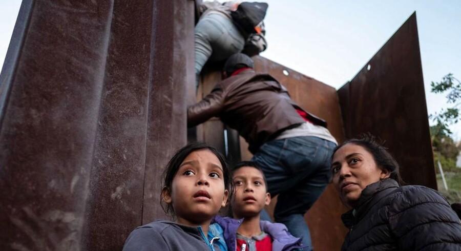 Migranter fra Centralamerika forsøger at krydse et hegn ved den amerikansk-mexikanske grænse.