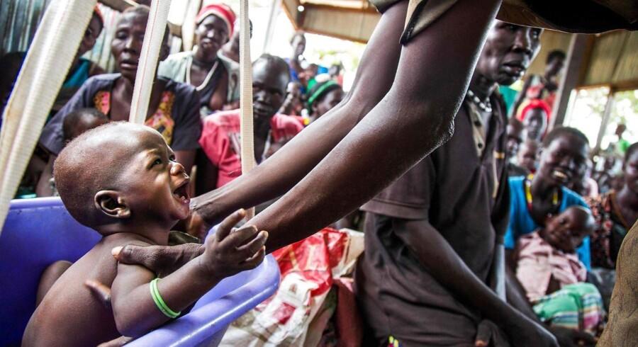 En moder vejer sit underernærede barn i et center drevet af International Rescue Committee (IRC) i Panthau, Sydsudan. Ved at indføre en milliardærskat kan man udrydde verdens fattigdom, mener Djaffar Shalchi og Tim Whyte.