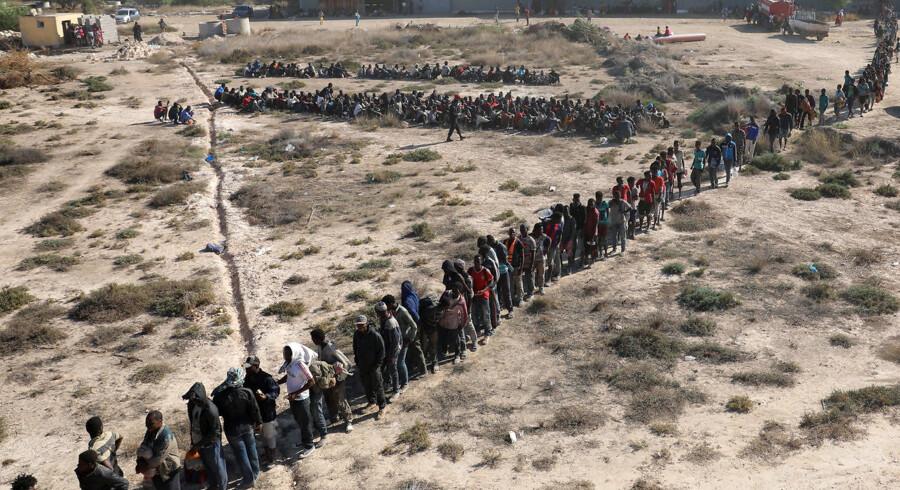 Migranter i Libyen afventer transport til et detentionscenter. (Arkivfoto)