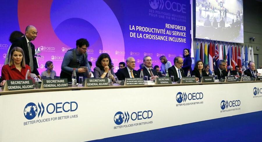 Ministre og delegerde omkring OECDs generalsekretær Jose Angel Gurria på onsdagens møde i OECD