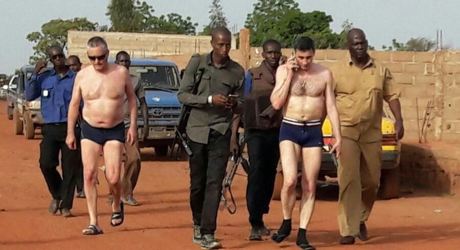 Maliske sikkerhedsstyrker eskorterer et par af de befriede gidsler i sikkerhed ved feriestedet Campement Kangaba nær Bamako, hvor militante islamister søndag dræbte fire civile og en soldat. Scanpix/Fototala King Massassy