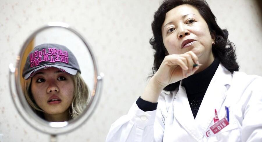 Plastikkirurgien i Kina er i så kraftig vækst, at branchen om få år ventes at have en markedsværdi på 800 milliarder kroner. Den 21-årige kvinde på billedet har valgt at lægge sig under kniven hos denne kirurg i Shanghai. Målet er, »at komme til at ligne skuespillerinden Jessica Alba.«