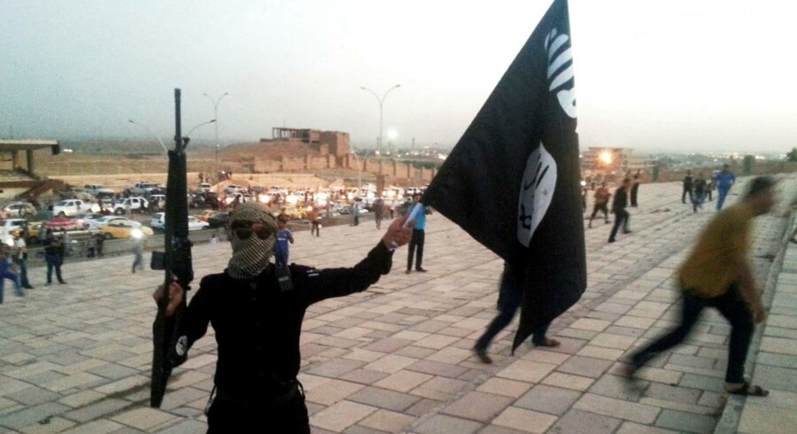 En jihadist fra islamisk stat holder et Islamisk Stat-flag og et våben i vejret i Mosul. REUTERS/Stringer/File Photo