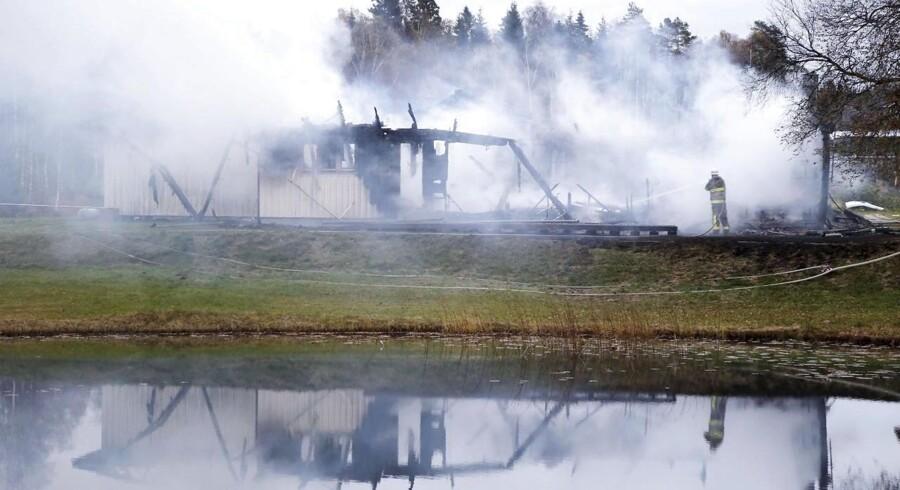 En brandmand kæmper mod flammerne i et asylcenter nær Munkedal i Sverige.