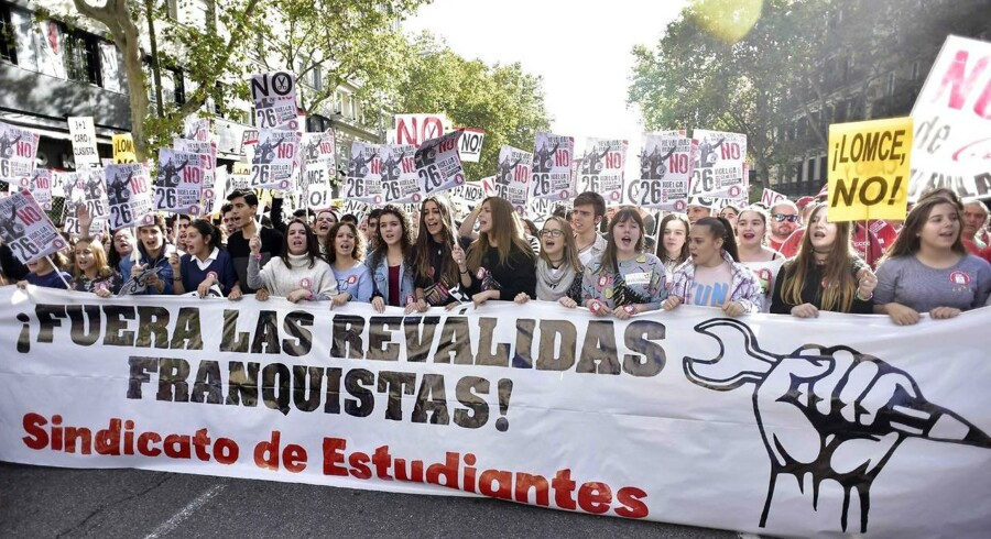 """Students hold a banner reading """"Out with the Franquist revalidation"""" Union"""" during a strike action called by the student union, in Madrid on October 26, 2016 against university entry exams dubbed """"revalidation"""" that the ruling Popular Party government voted into practice last summer, dubbing them as """"Franquist"""" and with the aim of, """"expel from the education system hundreds of thousands of young people from poor families"""". / AFP PHOTO / GERARD JULIEN"""