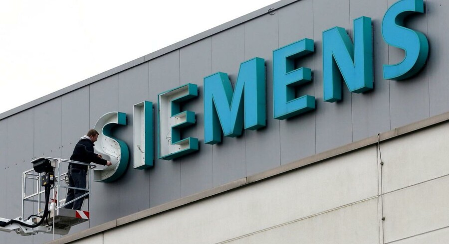 Arkivfoto: Mand arbejder på Siemens logo.
