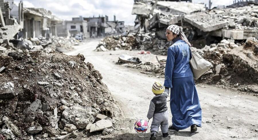 En kurdisk-syrisk kvinde går med sin barn gennem ruinerne i den syriske by Kobane, som IS blev drevet ud af i marts 2015.