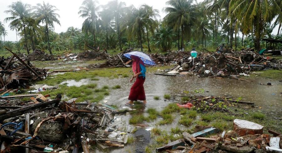 En kvinde går gennem det tsunamihærgede landskab på det vestlige Java i Indonesien.