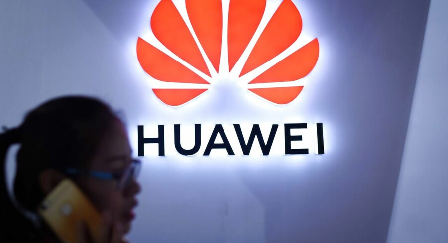 (FILES) In this file photo taken on July 08, 2018 (FILES) In this file photo taken on July 8, 2018 a woman uses her mobile phone in front of a Huawei logo at Beijing International Consumer Electronics Expo in Beijing. - Chinese telecom giant Huawei's chief financial officer faces US fraud charges related to sanctions-breaking business dealings with Iran, a Canadian court heard on December 7, 2018, a week after she was detained on an American extradition request. (Photo by WANG ZHAO / AFP)