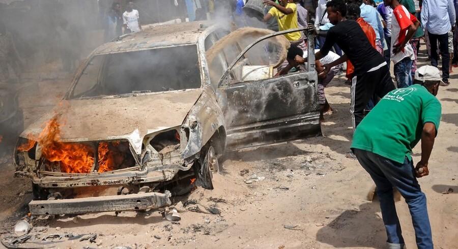 Somaliere kaster sand på en bil for at stoppe en brand efter en bilbombe i Mogadishu 16. december 2018. Mindst en person blev såret.