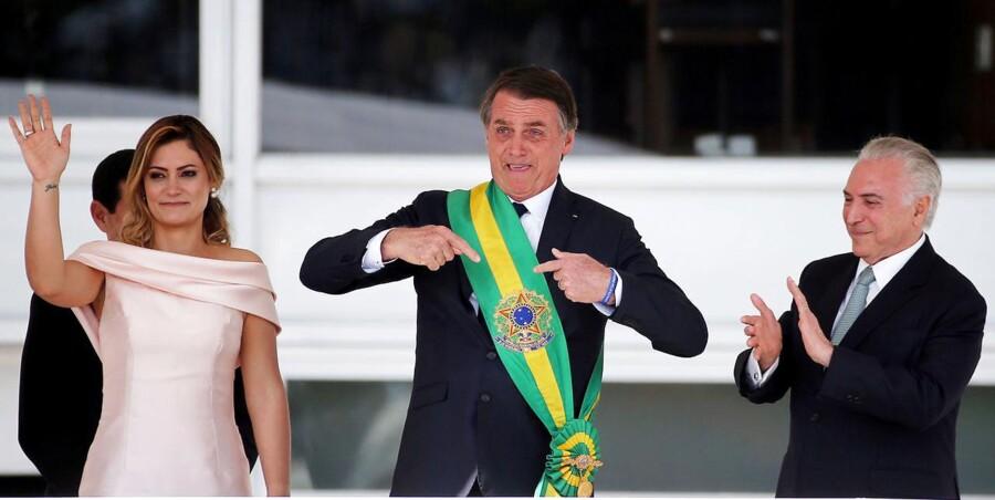 Brasiliens nye præsident, Jair Bolsonaro, modtager det præsidentielle skærf af sin forgænger, Michel Temer (t.h.), mens hans kone, Michelle Bolsonaro, vinker til de forsamlede tilhængere.