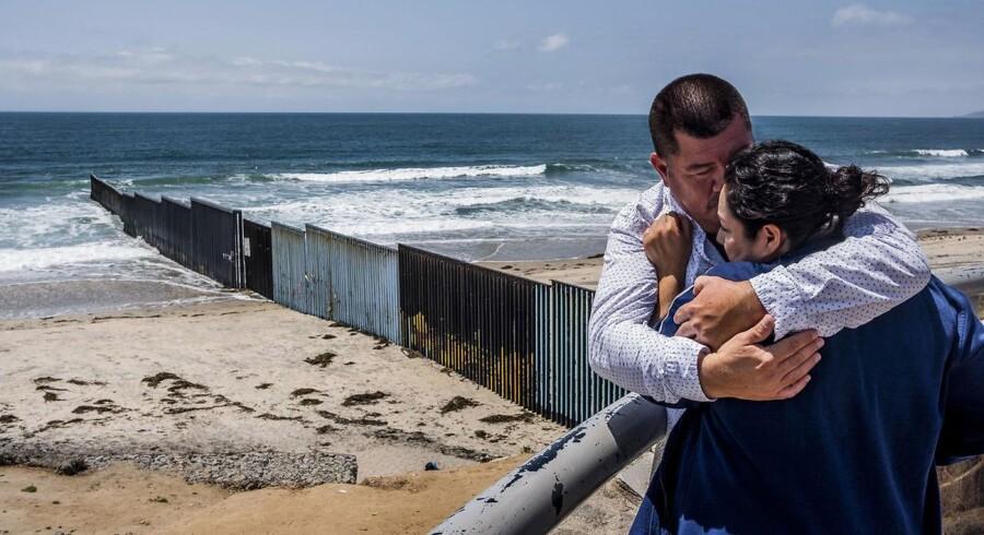 En mand krammer og trøster sin kone ved det høje hegn på grænsen, der fortsætter ud i stillehavet, mellem USA og Mexico. I dag er der et op til seks meter højt hegn langs 1.100 km af den 3.200 km lange grænse, omfattende elektronisk overvågning og tusindvis af patruljerende grænsebetjente. Trump forlanger at få en mur på hele grænsen.