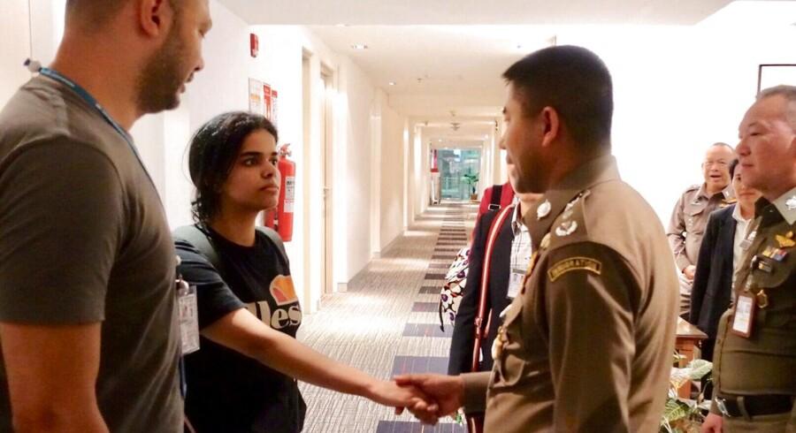 Saudiske Rahaf Mohammed al-Qunun giver hånd til thailandske immigrationsbetjente. De thailandske myndigheder vendte på en tallerken og bremsede hendes udvisning, efter at hun fik opmærksomhed fra både FN, Human Rights Watch og Australiens regering.