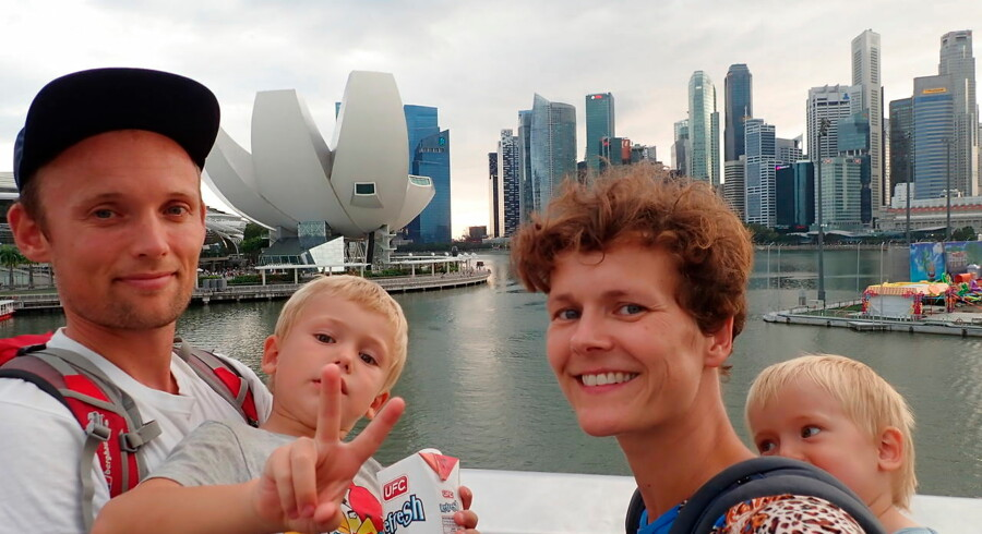 Christian Halleløv, Henriette Friis, Svend og Harly på en familie-selfie i Singapore, I baggrunden ses Singapores skyline og Singapore Art Museum.