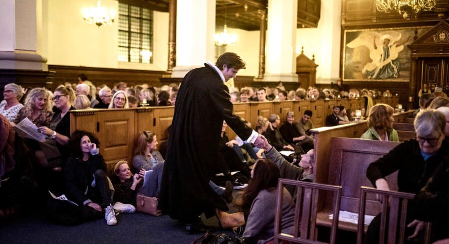 Præst Jens Biegel-Fogh hilser på de fremmødte, der er kommet for at synge Simon & Garfunkel ved fællessangsgudstjenesten i Helligåndskirken i København.