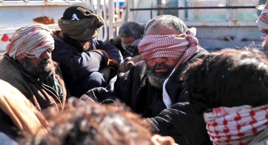 En gruppe mænd, angiveligt IS-krigere på flugt fra fronten, sidder bag i en lastbil efter at være taget til fange nær grænsen til Irak af SDF, koalitionsstyrken af især kurdiske og syriske tropper.