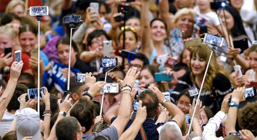 Smartphonen er blevet symbol på en voldsom digitalisering og et eksplosivt voksende dataforbrug, der skaber et hastigt voksende klimaaftryk. Her stimler filmende fans sammen om Paven, der ankommer til Vatikanet.