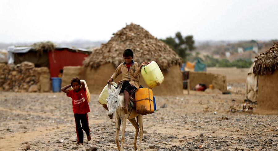 ARKIVFOTO: To drenge transporterer vanddunke tilbage til deres lejr i Abs i den nordlige provins Hajja, Yemen.