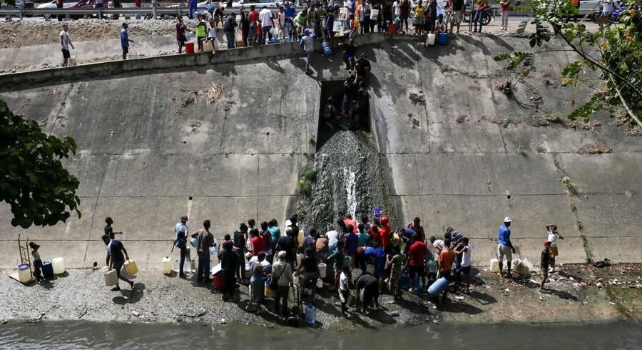 Folk i Venezuelas hovedstad Caracas henter vand fra en en rørledning ved floden Guaire, efter at et stort strømnedbrud har påvirket hele landet og har kostet flere menneskeliv. Nu hjemkalder USA alle sine tilbageværende diplomater fra det kriseramte land. Foto: Cristian HERNANDEZ / AFP)