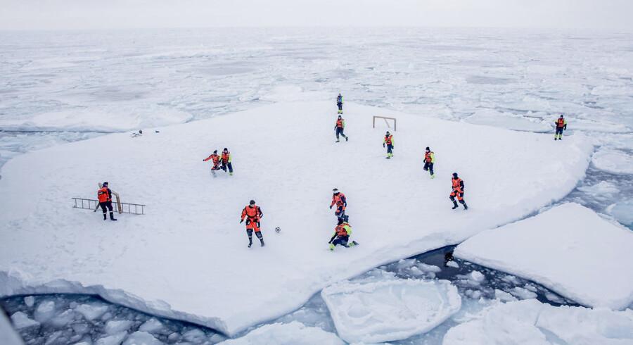 Forskere og flådefolk spiller fodbold på en isflage ud for Grønland. Temperaturen stiger kraftigere i Arktis end i resten af verden. Det skyldes især, at den forsvindende havis blotter mørke havområder, som suger solenergi til sig. Dermed ender Arktis i en opvarmningsspiral.