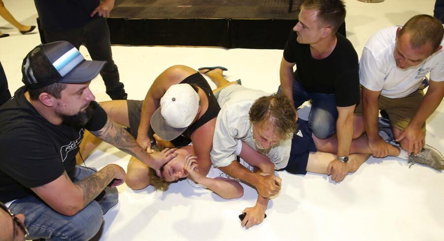 Tilhængere af den australske politiker Fraser Anning holder den 17-årige aktivist will Connolly nede efter Connolly kastede et æg i hovedet på Anning.