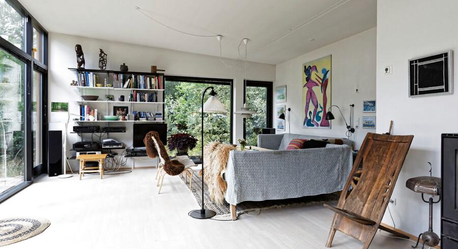 Stue med vinduer til gulvet mod syd og vest. Sofaen har Mette Hilden syet betræk til. Plakaten er af Ursula Reuter, og stolen af eksotisk afrikansk træ. Stole er Bruno Mattson-design.