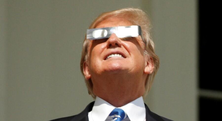 USAs præsident Donald Trump viser stigende interesse for rummet og for Amerikas bedrifter hinsides jordkloden. Her studerer han gennem beskyttelsesbriller solformørkelsen over USA 21. august 2017.