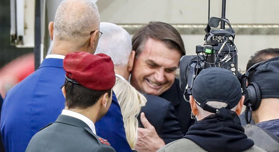 Brasiliens præsident, Jair Bolsonaro (i midten), omfavnes af Israels premierminister, Benjamin Netanyahu, ved ankomsten til lufthavnen i Tel Aviv søndag. Det er Bolsonaros første besøg i landet, siden han blev indsat som præsident. Jack Guez/Ritzau Scanpix