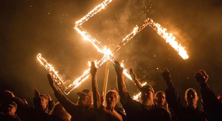 Tilhængere af den yderligtgående amerikanske National Socialist Movement hilser med strakt højrearm foran et brændende hagekors. Mødet blev afviklet på et hemmeligt sted i Georgia 21. april 2018.