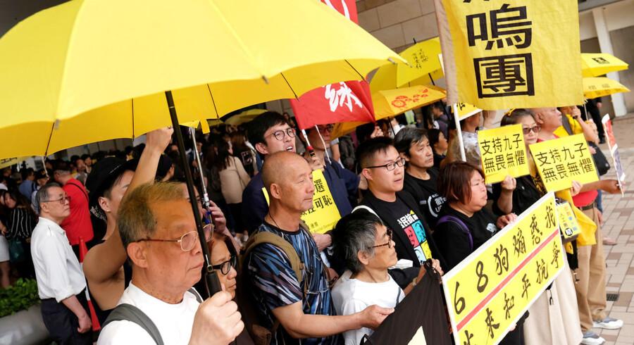 Demonstranter viser foran retten deres støtte til de ni protestledere, der tirsdag er blevet kendt skyldige i at stå bag demonstrationer i Hongkong i 2014. Paraplyerne var et særligt kendetegn for demonstrationerne. - Foto: Tyrone Siu/Reuters