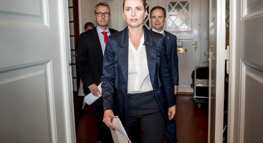 Mette Frederiksen, Henrik Sass Larsen og Nicolai Wammen på vej til pressemøde for at præsentere deres økonomiske plan.