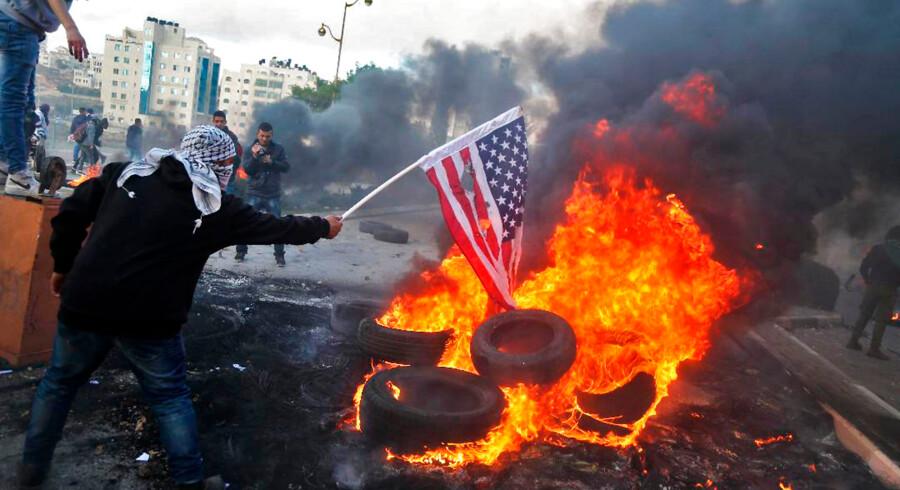 En palæstinensisk demonstrant på Vestbreden brænder et amerikansk flag under sammenstød med israelske soldater som en protest mod Donald Trumps beslutning om at anerkende Jerusalem som Israels hovedstad.