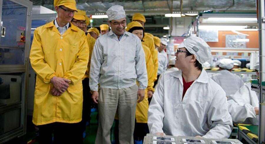 Apple får produceret sine iPhone-telefoner i Kina hos Foxconn. Her er Apple-topchef Tim Cook (til venstre i gult beskyttelsestøj) i 2012 på besøg hos Foxconn i Zhenzhou i Henan-provinsen for at inspicere produktionen.