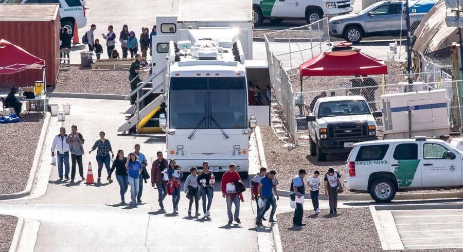 Migranter på vej ind i busser, som skal køre dem videre til sheltere.