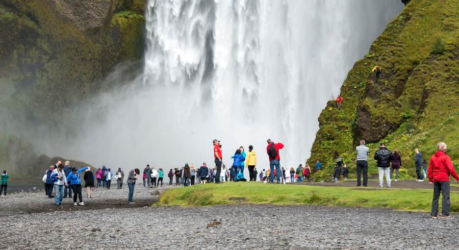 Turister besøger vandfaldet ved Skogar.