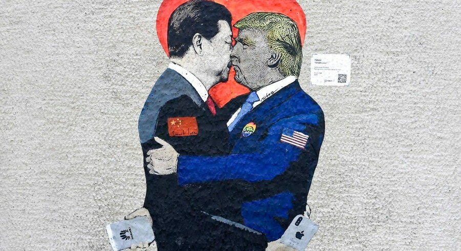 Et streetart-værk og karikatur af den italienske kunstner TvBoy er malet på væg i Milano. Kinas præsident Xi Jinping holder en (amerikansk) iPhone, mens USAs præsident Trump holder en (kinesisk) Huawie-telefon.