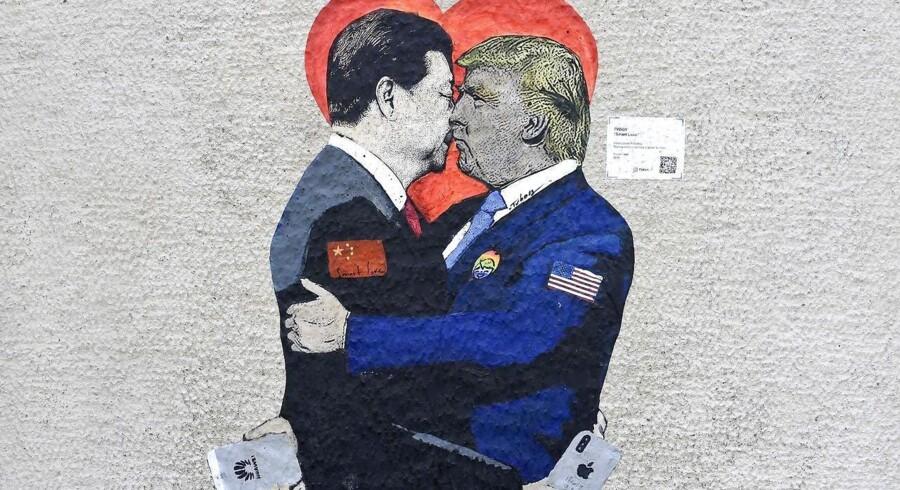 Med tydelig reference til det berømte dødskys, som Sovjetunionens præsident Leonid Bresjnjev gav den østtyske leder Erich Honecker, og som er afbildet på et tilbageværende stykke af Berlinmuren, har den italienske gadekunstner TvBoy fanget, at Kinas præsident, Xi Jinping (til venstre) med en amerikansk iPhone i hånden, kysser USAs præsident Donald Trump, som holder en kinesisk Huawei-telefon efter weekendens forhandlinger mellem de to i Japan. Foto: Miguel Medina, AFP/Ritzau Scanpix