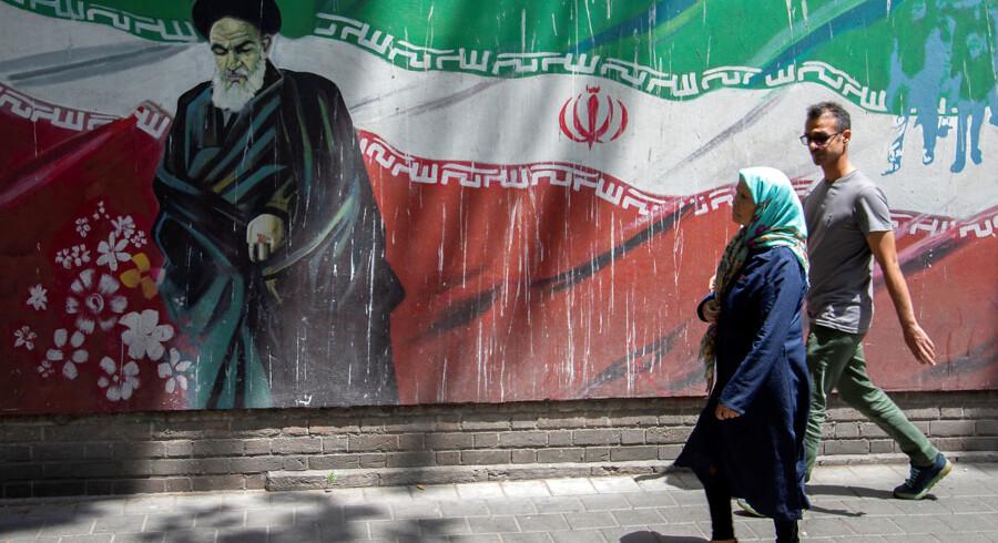 Folk går forbi et revolutionsbillede af den afdøde ayatollah Ruhollah Khomeini.