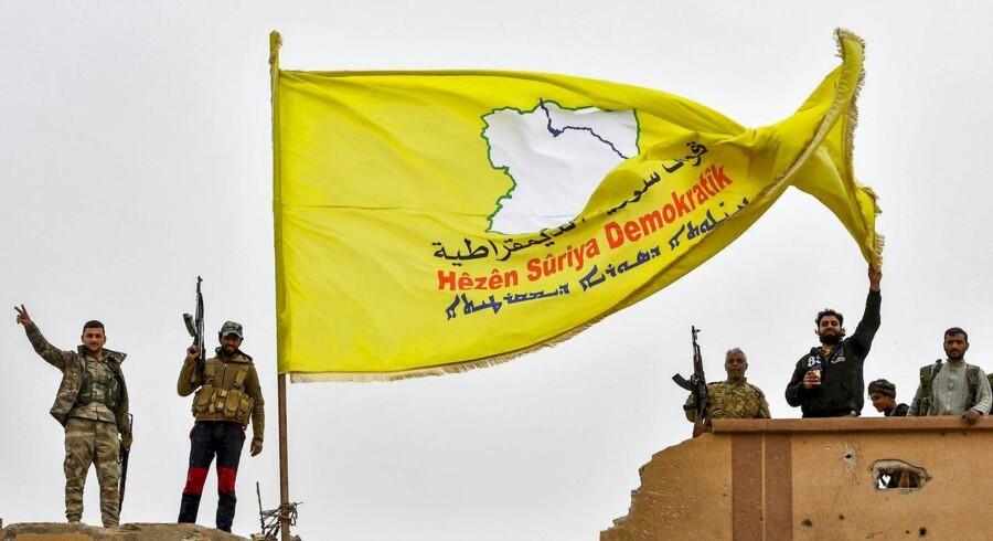 USA vil have tropper fra Danmark og andre europæiske lande til at afløse amerikanske soldater i det nordøstlige Syrien, hvor de støtter Syriens Demokratiske Styrker (SDF), der er ført an af kurdiske styrker. Her hejser SDF-styrker et flag over en bygning i Baghouz, der blev befriet fra Islamisk Stat i marts.