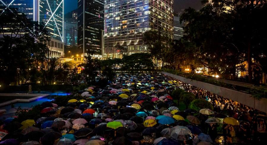 Adskillige befolkningsgrupper i Hongkong har sommeren over demonstreret mod regeringen og en lov om udlevering til Kina. På billeder holder folk fra finansmiljøet paraplyer op under en protest i regnvejr 1. august 2019. Fredag aften går statsligt ansatte højst opsigtsvækkende også på gaden.