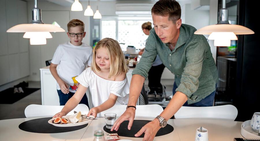 Victoria på 11 hjælper sin far Morten, 42, med at rydde bordet efter morgenmad.