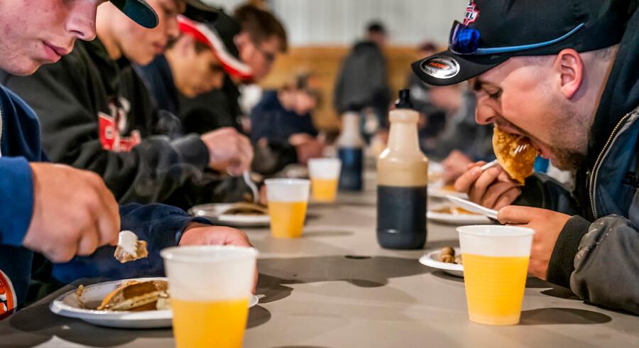 Ved bordene i laden går snakken om Trumps handelskrig, mens der spises pandekager med et ordentligt lag sirup.