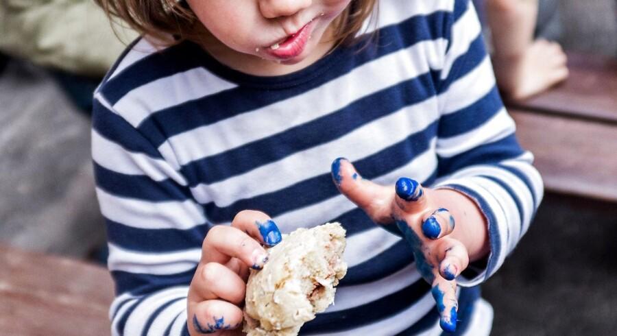 Pige spiser bolle i børnehave i København.