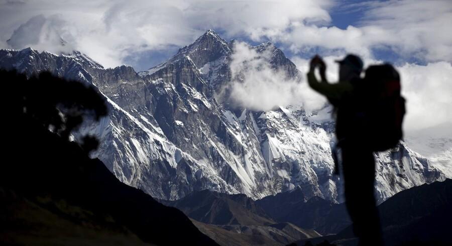 En turist tager et billede af Mount Nuptse (i midten), mens Mount Everest er dækket af skyer (tv.). I år har kun en enkelt vovehals gjort forsøget på at bestige Everest, nemlig den 33-årige japaner Nobukazu Kuriki. I begyndelsen af oktober nåede han op i ca. 8.100 meters højde, før han gav op på grund af kraftig vind og overvældende snemængder.